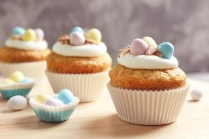 Decorated Easter Cupcakes On Wooden Table Against Grey Backgroun